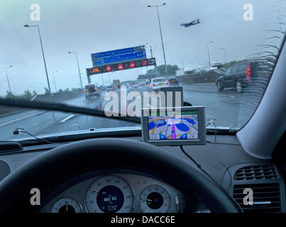 M25 Orbital at Heathrow airport in rain conditions with aircraft on final approach red speed hazard lights on information - Stock Photo