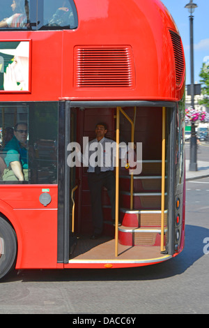 Bus conductor on the hop on hop off platform of the new London double decker Boris routemaster bus - Stock Photo
