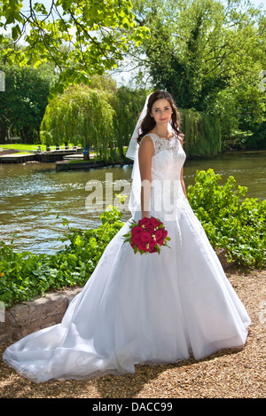 Bride in traditional white bridal dress with red rose bouquet just married, posing in riverside church grounds - Stock Photo