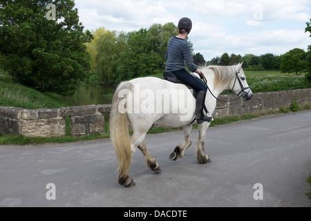 Young Woman riding through the village of Reybridge - Stock Photo