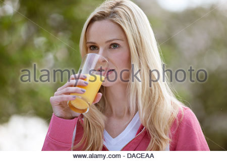 A young woman drinking a glass of orange juice outside - Stock Photo