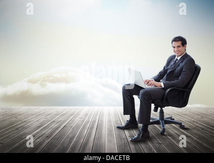 Handsome businessman sitting on a swivel chair and using his laptop - Stock Photo