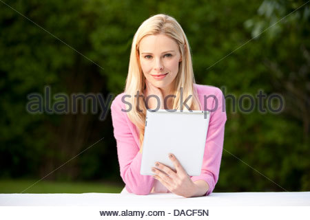 A young blond woman sitting at a garden bench holding a digital tablet - Stock Photo