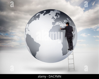 Businessman on a ladder drawing on a planet - Stock Photo