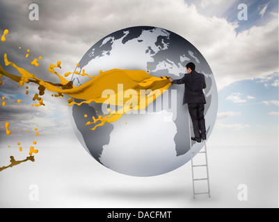 Businessman on a ladder drawing on a planet with paint - Stock Photo