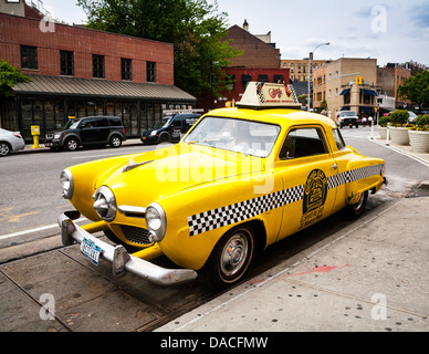 Old 1950's Studebaker yellow taxi used to advertise the Caliente restaurant, Greenwich Village, New York City, USA - Stock Photo