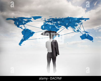 Businessman with an umbrella looking at a world map - Stock Photo