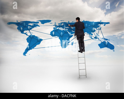 Businessman standing on a ladder drawing a world map - Stock Photo