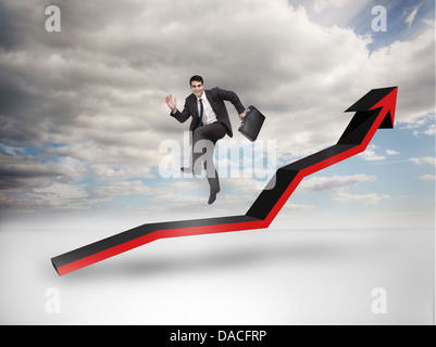 Businessman jumping over a red arrow pointing up - Stock Photo