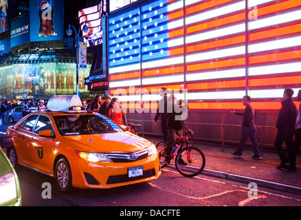 Illuminated Stars and Stripes flag with taxi, Times Square, Manhattan, NYC, USA. - Stock Photo