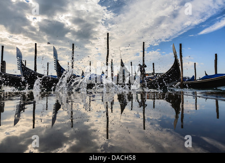 Gondolas with reflection and water splash, Venice, Italy - Stock Photo
