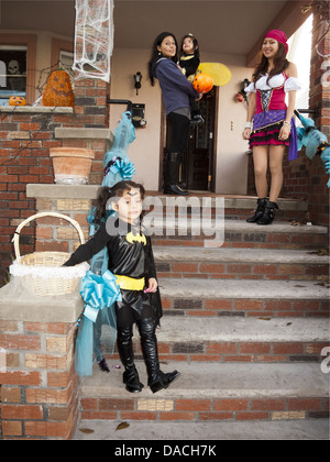 Halloween in the Kensington section of Brooklyn, NY, 2010. Costumed family waits to give out candy to trick-or-treaters. - Stock Photo