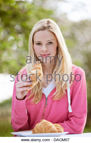 A young woman eating a croissant outside - Stock Photo