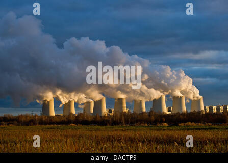 The setting sun illuminates cooling towers of a brown coal power station of the power company Vattenfall in Jaenschwalde, - Stock Photo
