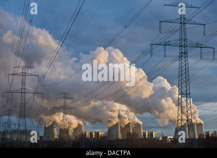 The setting sun illuminates cooling towers of a brown coal power station of the power company Vattenfall, that are - Stock Photo