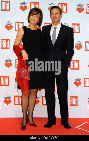 Maybrit Illner and Rene Obermann arrive for the fundraising event 'Ein Herz fuer Kinder' ('A Heart for Children') - Stock Photo