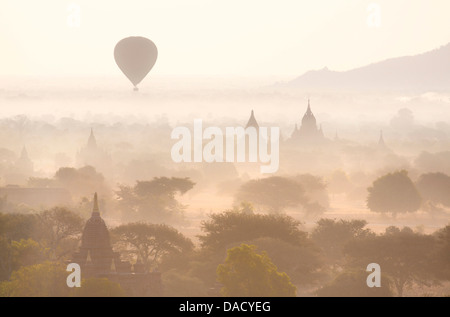 Temples of Bagan swathed in morning mist, with hot air balloon drifting across the scene, from Shwesandaw Paya, - Stock Photo