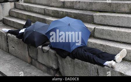 Two pupils take shelter from rain underneath an umbrella in Osaka, Japan, 18 November 2011. Photo: Angelika Warmuth - Stock Photo