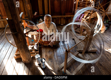 Woman spinning silk in factory in In Phaw Khone village, Inle Lake, Myanmar (Burma), Southeast Asia - Stock Photo