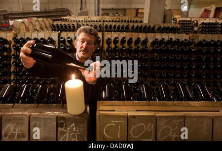 Taster Konrad Scheerbaum rotates the sparkling wine bottles at the State Vineyard Castle Wackerbarth in Radebeul, - Stock Photo