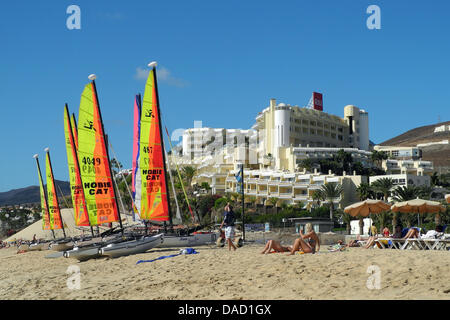 Small sailing boats lie on the sandy beach of Jandia in front of the 'Riu Palace Jandia' hotel in Morro Jable on - Stock Photo