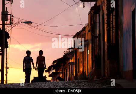 Two young people in silhouette at sunset on cobbled street, Trinidad, UNESCO Site, Cuba, West Indies, Central America - Stock Photo