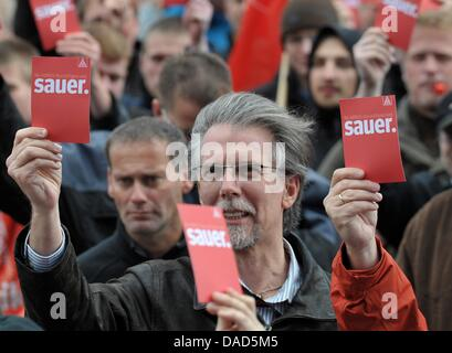 Airbus employees hold up cards saying 'sauer' (mad) at a protest organised by German metalworkers' union IG Metall - Stock Photo