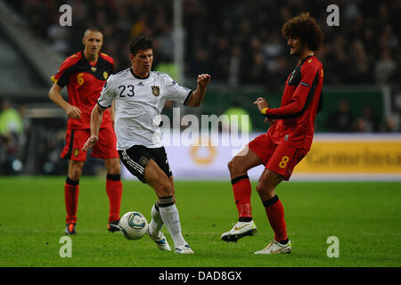 Belgium'sMarouane Fellaini (R) vies for the ball with Germany's Mario Gomez during the Group A EURO 2012 qualifying - Stock Photo