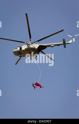 A helicopter with the syrian flag hovers above thousands of Syrians during a pro-government rally at Saba Bahrat - Stock Photo