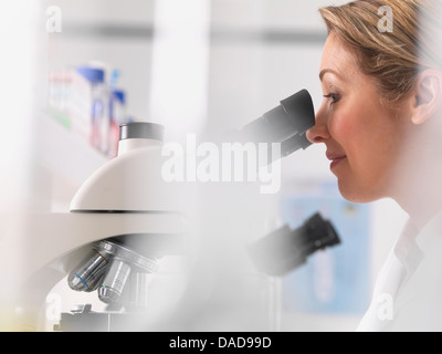 Female microbiologist viewing specimen under microscope in lab - Stock Photo