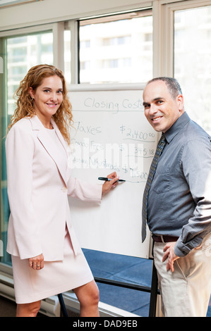 Real estate agent using flip chart with closing cost data - Stock Photo
