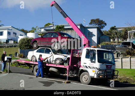 Man towing damaged car over a tow truck - Stock Photo