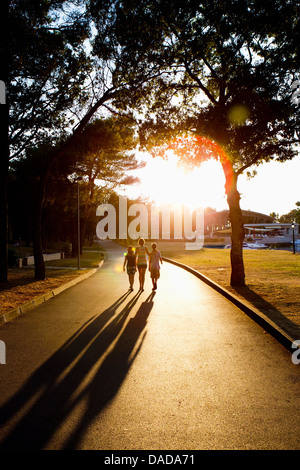 Mother and children walking on path in sunlight - Stock Photo