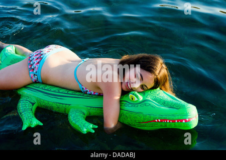 ... Girl In Sea With Inflatable Crocodile   Stock Photo