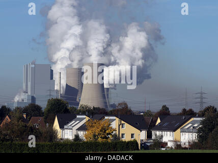 Smoke and water vapor rise from the cooling towers and chimneys of the NeurathII brown coal power station owned - Stock Photo