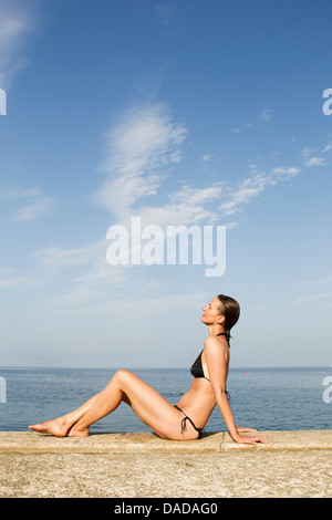 Woman sitting on wall by the sea - Stock Photo