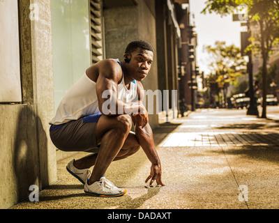Runner crouching on street - Stock Photo