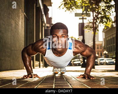 Young man doing push-up on city street - Stock Photo