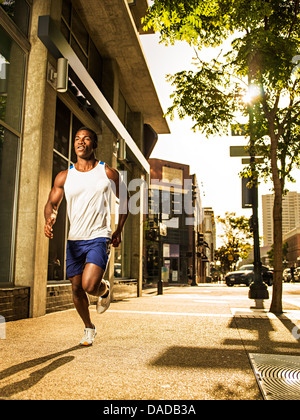 Young man running on city street - Stock Photo