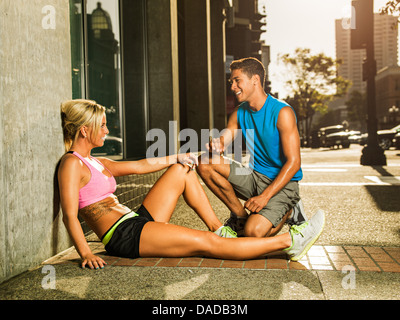 Female and male runners sitting on sidewalk - Stock Photo