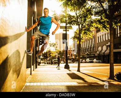 Young man practising parkour - Stock Photo