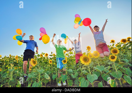 Jumping kids on field in summer time - Stock Photo