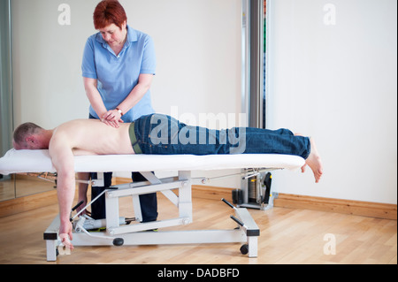 Man lying on front on massage table getting message - Stock Photo