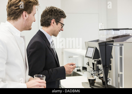 Man wearing business attire getting drink from coffee machine - Stock Photo