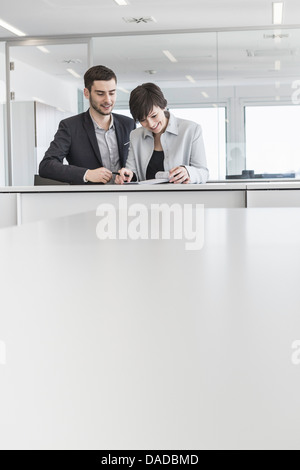 Businesspeople standing doing paperwork in office - Stock Photo