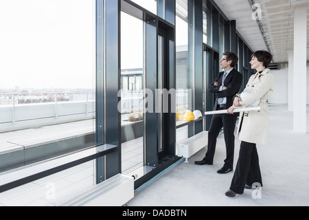 Architects looking out of window with blueprint - Stock Photo