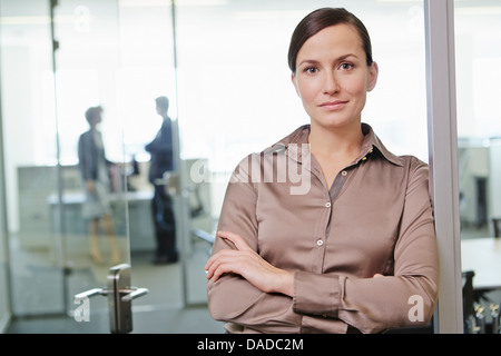 Mid adult woman standing in office with arms crossed - Stock Photo
