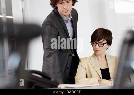 Businesswoman sitting at desk, man looking over her shoulder at paperwork - Stock Photo
