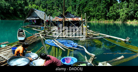 huts on Chiao Lan reservoir, women washing the dishes, Thailand, Khao Sok National Park - Stock Photo