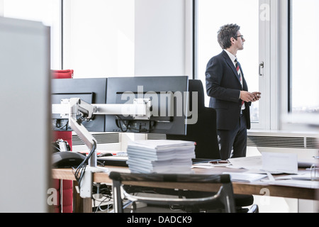Businessman standing in office looking out of window - Stock Photo